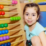 Cute little girl playing with abacus in kindergarten