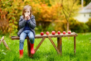 Cute little girl sitting on a wooden bench on autumn day